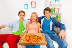 Muchacha que sostiene la pizza en el cartón y los muchachos que se sientan cerca Foto de archivo