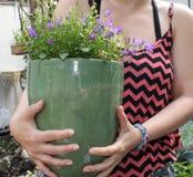 Muchacha que sostiene la planta en conserva Fotografía de archivo libre de regalías