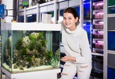 Muchacha que sostiene la red del acuario y el envase del agua al lado del acuario w Fotos de archivo libres de regalías
