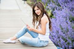 Muchacha que sostiene la tableta al aire libre Fotografía de archivo libre de regalías