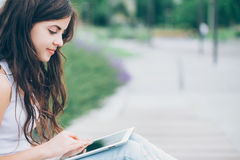 Muchacha que sostiene la tableta al aire libre Fotografía de archivo