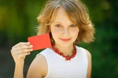 Muchacha que sostiene la tarjeta del crédito en blanco al aire libre Fotos de archivo