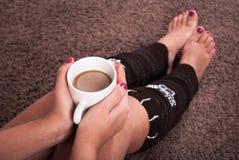 Muchacha que sostiene la taza de café disponible en rodillas y que se sienta en moqueta foto de archivo libre de regalías