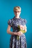 Muchacha que sostiene las flores en un fondo azul imágenes de archivo libres de regalías