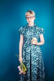 Muchacha que sostiene las flores y el cráneo en un fondo azul Imágenes de archivo libres de regalías