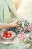 Muchacha que sostiene las fresas frescas en una placa En el sofá en la sala de estar acogedora Accesorios para hacer punto de la  Foto de archivo libre de regalías