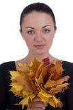 Muchacha que sostiene las hojas de arce anaranjadas del otoño en blanco foto de archivo
