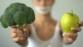Muchacha que sostiene las verduras, dieta baja en carbohidratos, alimento biológico de recomendación del vegetariano almacen de metraje de vídeo