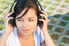 Muchacha que sostiene los auriculares y que escucha la música Foto de archivo