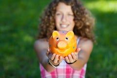 Muchacha que sostiene Piggybank en parque Imágenes de archivo libres de regalías