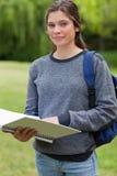 Muchacha que sostiene su cuaderno mientras que lleva su backp Imagenes de archivo