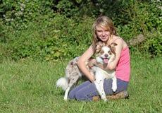 Muchacha que sostiene su perro del border collie. Imagen de archivo
