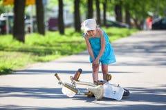 Muchacha que sostiene su rodilla después de caer abajo Fotografía de archivo libre de regalías