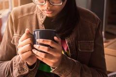 Muchacha que sostiene un café en el trabajo Foto de archivo