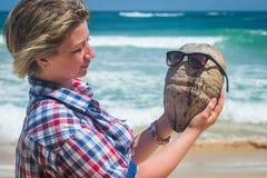 Muchacha que sostiene un coco en la playa tropical del océano Imagen de archivo libre de regalías