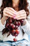 Muchacha que sostiene un manojo grande de uvas rojas foto de archivo libre de regalías