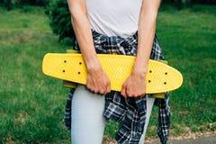 Muchacha que sostiene un monopatín plástico amarillo en el parque Imagenes de archivo