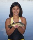 Muchacha que sostiene un pescado Fotografía de archivo