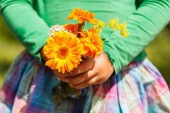 Muchacha que sostiene un ramo de flores anaranjadas Foto de archivo
