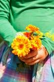 Muchacha que sostiene un ramo de flores anaranjadas Imágenes de archivo libres de regalías