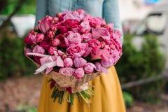 Muchacha que sostiene un ramo de flores rosadas fotografía de archivo