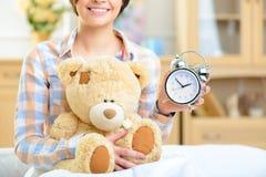 Muchacha que sostiene un reloj y un oso de peluche grande Fotografía de archivo libre de regalías