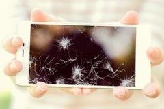 Muchacha que sostiene un teléfono elegante quebrado Imagen de archivo