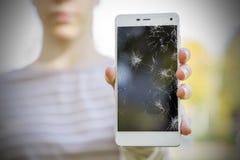 Muchacha que sostiene un teléfono quebrado Fotos de archivo libres de regalías