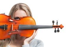 Muchacha que sostiene un violín y que mira a través de él Imágenes de archivo libres de regalías