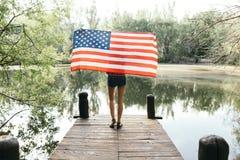 Muchacha que sostiene una bandera americana en naturaleza Imagen de archivo libre de regalías