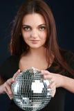 Muchacha que sostiene una bola brillante del disco Foto de archivo libre de regalías