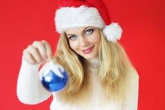 Muchacha que sostiene una bola de la Navidad Fotos de archivo