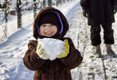 Muchacha que sostiene una bola de nieve imagenes de archivo
