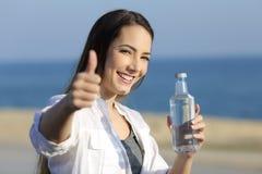 Muchacha que sostiene una botella de agua que gesticula el pulgar para arriba en la playa Fotos de archivo libres de regalías