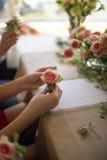 Muchacha que sostiene una flor en masterclass de la flor Imagen de archivo