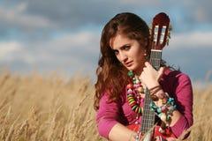 Muchacha que sostiene una guitarra en campo Imagenes de archivo