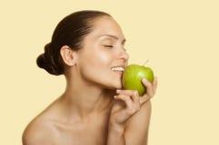 Muchacha que sostiene una manzana cerca de los labios Foto de archivo
