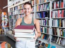 Muchacha que sostiene una pila de libros en una librería Fotos de archivo libres de regalías