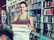 Muchacha que sostiene una pila de libros en una librería Imagen de archivo