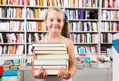 Muchacha que sostiene una pila de libros en una librería Fotografía de archivo libre de regalías