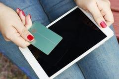 Muchacha que sostiene una tarjeta de crédito en su mano y tableta, aire libre, concepto de compras en línea, lunes cibernético fotos de archivo