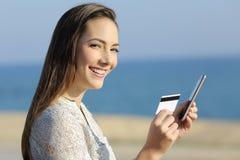 Muchacha que sostiene una tarjeta y un teléfono de crédito que miran la cámara Imagenes de archivo