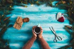 Muchacha que sostiene una taza de cacao caliente en fondo del azul de la Navidad Imágenes de archivo libres de regalías