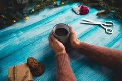 Muchacha que sostiene una taza de cacao caliente en fondo del azul de la Navidad Imagenes de archivo