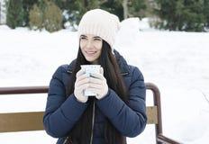 Muchacha que sostiene una taza de té en el fondo de agujas verdes foto de archivo libre de regalías
