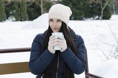 Muchacha que sostiene una taza de té en el fondo de agujas verdes fotografía de archivo