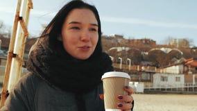 Muchacha que sostiene una taza disponible de café y de hablar almacen de video