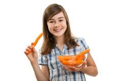 Muchacha que sostiene zanahorias frescas Imágenes de archivo libres de regalías