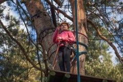 Muchacha que sube en el parque de la aventura, parque de la cuerda Imagen de archivo