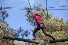 Muchacha que sube en el parque de la aventura, parque de la cuerda Foto de archivo